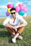 Posadzony przypadkowy mężczyzna z balonami i okularami przeciwsłonecznymi zdjęcia stock