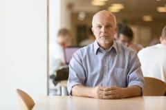 Posadzony starszy mężczyzna spokojnie patrzeje zdjęcia stock