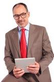 Posadzony stary szczęśliwy biznesmen trzyma pastylka ochraniacza zdjęcia royalty free