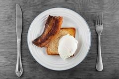 Poschiertes Ei mit Toast und Speck stockbild