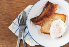 Poschiertes Ei mit Toast und Speck stockfotografie