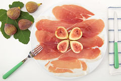Posciutto with figs on white table Royalty Free Stock Photo