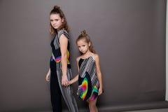 Pose à la mode de deux filles sur un fond gris Photo stock