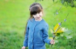 Pose adorabili della ragazza del bambino all'aperto con i fogli Fotografia Stock