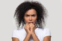Pose africaine de froncement de sourcils de femme au-dessus du blanc gris regardant la cam?ra images libres de droits