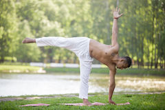 Pose Ardha Chandrasana. Serene attractive Indian young man in white linen clothes working out on lake in park, standing in ardha chandrasana (Half Moon Pose) royalty free stock photography