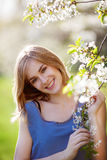 Pose assez blonde près d'un buisson fleurissant Photographie stock libre de droits