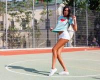 Pose assez jeune de fille de brune de hippie extérieure sur la rue dans les shorts blancs, une chemise de turquoise et les espadr Image libre de droits