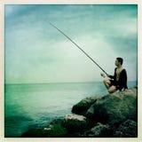 Pose avec un poteau de pêche Images stock