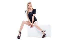 Pose blonde aux longues jambes gaie sur le cube Photos stock