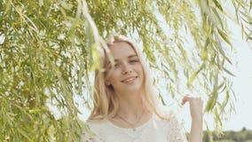 Pose blonde de jeune fille russe sur un fond des branches de saule clips vidéos