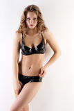 Pose blonde sensuelle dans la lingerie noire de latex Photographie stock