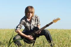 Pose d'adolescent de joueur de guitare Image libre de droits