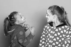 Pose d'enfants sur le fond rose Filles dans des pyjamas pointillés par polka Photographie stock libre de droits
