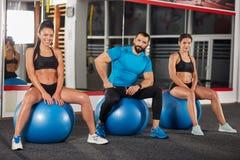 Pose d'entraîneur de forme physique et de deux filles photographie stock