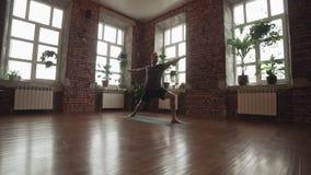 Pose da ioga do guerreiro da prática do homem no estúdio com parede de tijolo Homem desportivo que faz a ioga video estoque