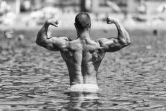 Pose de biceps dans la piscine Photos stock