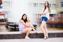 Pose de deux belle amies sur la rue Image libre de droits