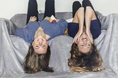 Pose de deux filles à l'envers sur un sofa gris à la maison souriant Photo libre de droits