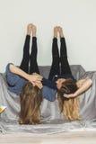 Pose de deux filles à l'envers sur un sofa gris avec des jambes  Photo libre de droits