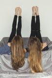 Pose de deux filles à l'envers sur un sofa gris avec des jambes  Photographie stock libre de droits
