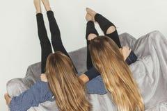 Pose de deux filles à l'envers sur un sofa gris avec des jambes  Photos libres de droits