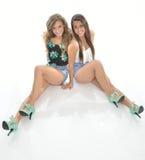Pose de deux jolie jeunes femmes dans des équipements occidentaux de pays Images libres de droits