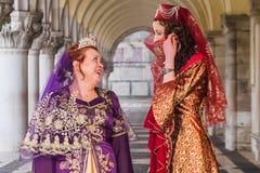Pose de duas mulheres sob arcos dos doges palácio, carnaval de Veneza Fotografia de Stock