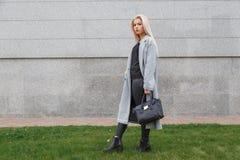 Pose de femme à la mode extérieure, tenant le sac en cuir noir, bottes élégantes de port, manteau élégant Concept femelle de mode photos stock