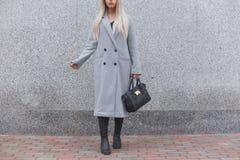 Pose de femme à la mode extérieure, tenant le sac en cuir noir, bottes élégantes de port, manteau élégant Concept femelle de mode images stock