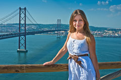 Pose de fille et la passerelle du 25 avril dans Lisbo Photo stock