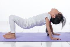 Pose de pratique chinoise asiatique de yoga de petite fille Photographie stock libre de droits