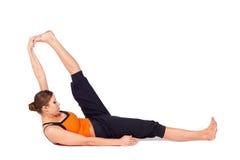 Pose de reclinação praticando da ioga do dedo grande do pé da mulher Fotografia de Stock