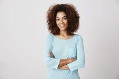 Pose de sourire de belle fille africaine avec les bras croisés photographie stock libre de droits