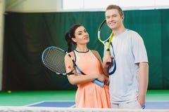 Pose de sourire heureuse de deux joueurs de tennis d'intérieur photos stock