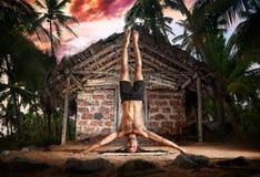 Pose de stand de tête de yoga près de hutte de pêcheur Images stock