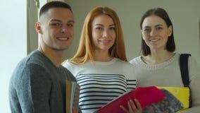 Pose de três estudantes na faculdade imagem de stock royalty free