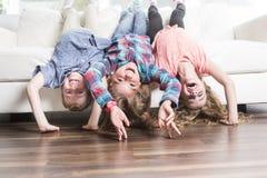 Pose de trois childs à l'envers sur un sofa blanc à la maison Photo stock