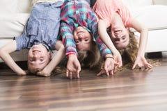 Pose de trois childs à l'envers sur un sofa blanc à la maison Image libre de droits