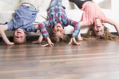Pose de trois childs à l'envers sur un sofa blanc à la maison Photos stock