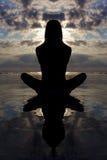 Pose de yoga de coucher du soleil avec la réflexion dans l'eau. Image libre de droits