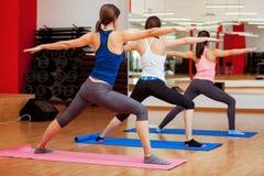 Pose de yoga de guerrier par des jeunes femmes Photographie stock libre de droits