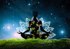 Pose de yoga de Lotus contre des cieux nocturnes Photo stock