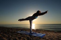 Pose de yoga du guerrier III sur la plage Images libres de droits