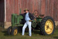 Pose del coltivatore con il suo trattore Fotografia Stock