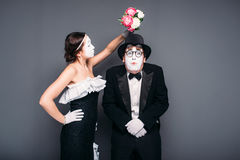 Pose dell'attore e dell'attrice della commedia con il mazzo del fiore Fotografia Stock