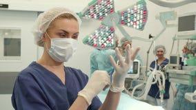 Pose dell'infermiere alla stanza della chirurgia video d archivio