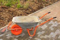 Pose des pavés Réparation du trottoir brouette image stock