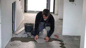 Pose des tuiles d'hexagone sur le plancher Enfoncement et réglementation banque de vidéos