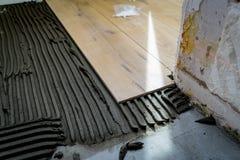 Pose des tuiles sur le plancher avec une colle spéciale photographie stock libre de droits